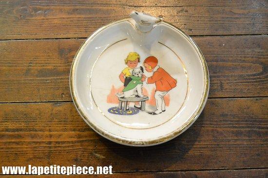 Assiette à bouillie en Porcelaine de Limoges, décor chien bouchon oiseau
